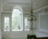 A view from the first floor landing at Peckover House, looking towards the Venetian window, showing the C18th ceiling and wall plasterwork and glass, and metal light fitting