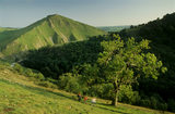 Hillside view of Thorpe Cloud rising behind a wooded ridge in Dovedale with ramblers in the foreground