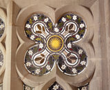 Close view of a quatrefoil stained glass window with sun design in the centre in the Chapel at Tyntesfield