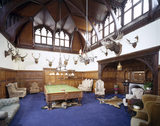 General view of Billiard Room at Tyntesfield taken towards the inglenook with stone & marble fireplace, carved oak panelling, recessed gothic windows and chandelier