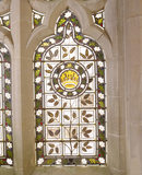 Detail of a stained glass window in the chapel at Tyntesfield with a crown motif and holly and ivy with Christmas roses round the edge