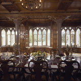Medium view of Dining Room at Tyntesfield towards lancet windows with carved stone gothic heads, carved oak panelled walls with cupboards underneath & flowers on table