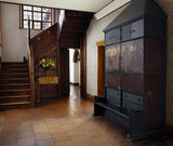 The Entrance Hall at Red House with a cupboard painted by William Morris and the oak staircase with its vertical tapered newel posts