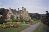 South West view of Tyntesfield, showing bow window of Drawing Room & arches of the loggia, formal flowerbeds along the terrace & towering roof of the Main Hall