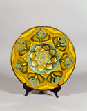 Della Robbia charger in the Morning Room at Standen, a piece of ceramic with stylised flower pattern in yellow, green and brown