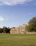View across the lawn to the South Front of Wimpole Hall with blue sky behind