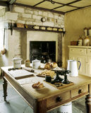 Room view of the Kitchen showing a large table, fireplace and range