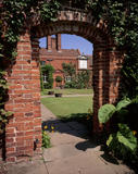 A view through the red brick archway to Packwood House showing a wall mounted sundial and two trimmed bay trees in containers