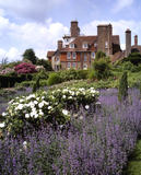 The east front of Standen seen from the garden, with purple and white flowers in the foreground