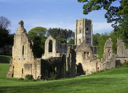 The ruins of the East Guest House with the Tower of Fountains Abbey behind it