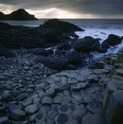 Hexagonal basalt rocks at Giants Causeway, light breaking through clouds out at sea