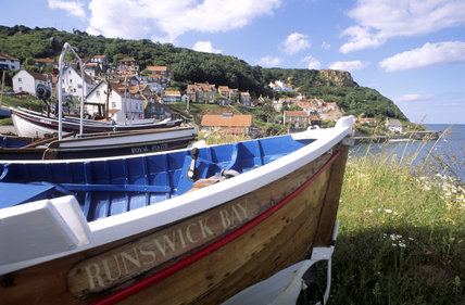 Runswick Bay, showing a boat in the foreground, with the Bay in the background