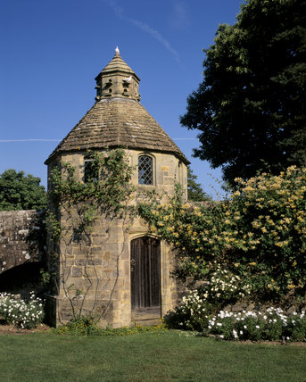 The Dovecote in Nymans Garden with honeysuckle climbing over the walls