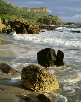 The tide sweeps in at Murlough Bay, Northern Ireland, while in the background Fairhead is visible