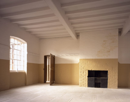 Men's Dayroom on ground floor showing the door, fireplace, window, hooks and part of ceiling timbers