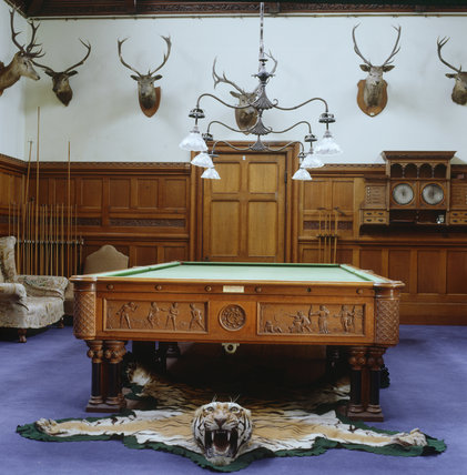 Billiard Room has carved oak panelling on the walls which are decorated with stags' heads