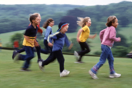A group of young children running across the grounds of Polesden Lacey. MR