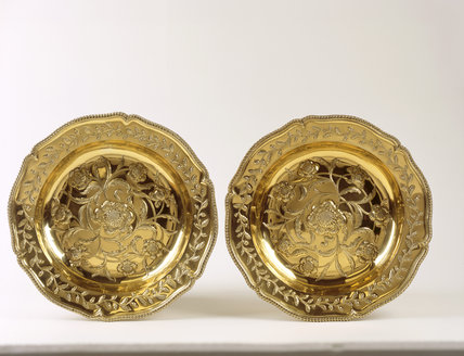 Two silver gilt chargers recovered after a theft in the 1990's, flowers in an entwined pattern on the base and similar leaf pattern round the edge