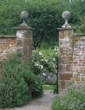 Looking through a stone gateway, in the grounds of Acorn Bank, leading between two parts of the garden