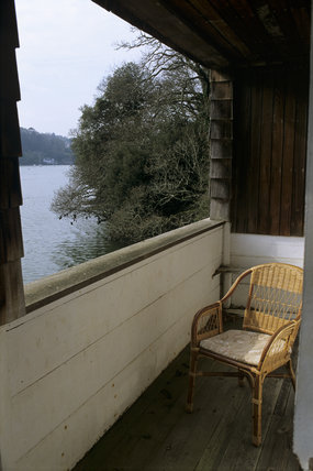 A wicker garden chair on the balcony of the boat house at Greenway