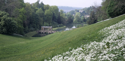Overall view of Prior Park showing the Palladian Bridge, 1755, over the lakes in the middle distance, beyond a grassy slope with wild garlic