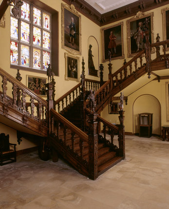 The Great Hall in Blickling Hall showing the staircase with Jacobean newel figures, paintings, relief of Anne Boleyn and late C18th