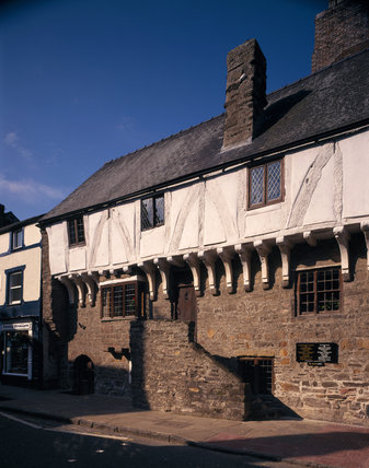 A view of the front of Aberconwy House showing the steps which jetties onto the street, front door, roof and chimney