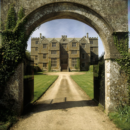 View of Chastleton House looking through the arch of the Entrance Gate showing the driveway leading to the house