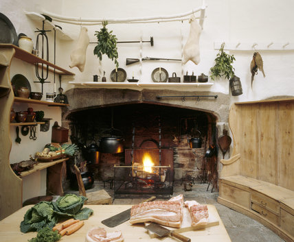 View of the Kitchen at Cotehele looking towards the open hearth, with a rack suspended from the ceiling and table with meat and vegetables