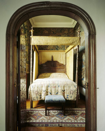 Room view into the Queen Anne's Room looking towards the bed which decorated with early Tudor carved, gilt and painted post and 17th century finials and headboard