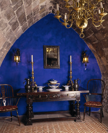 A view of the Dining Room, showing the blue wall, the steeply vaulted stone ceiling the Dutch C17th brass chandelier and the walnut Flemish side table