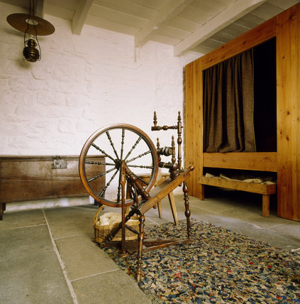 View from the window towards the bed and back wall showing the original doorway with spinning wheel