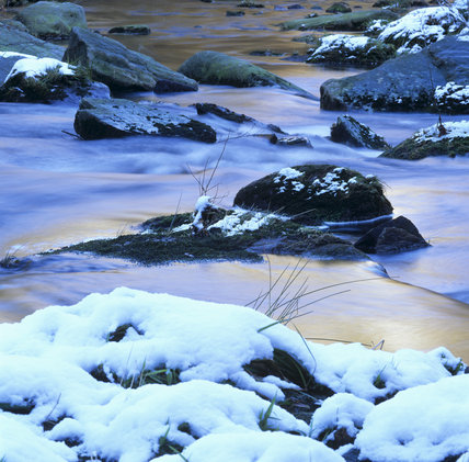 Hebden Water running through snow covered rocks at Hardcastle Crags