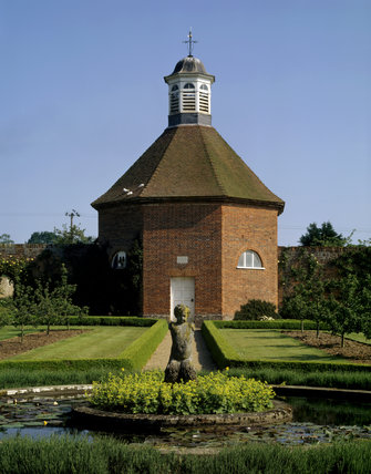 The Dovecote at Felbrigg Hall seen across a pond with a statue in the centre