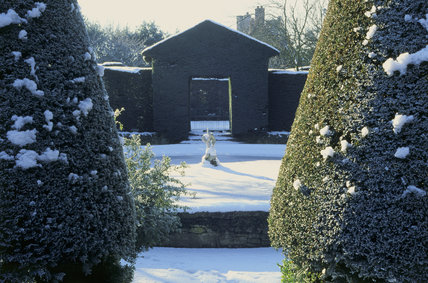 A view of the frozen and snow covered Bathing Pool Garden with the fountain head throwing a long shadow