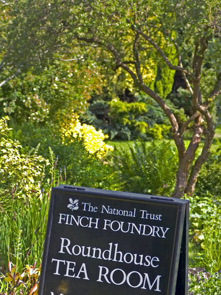 A sign in the garden at Finch Foundry, advertising the Roundhouse Tea Room