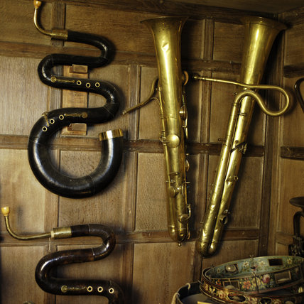 Two serpents and two ophicleide, part of the musical instrument collection at Snowshill Manor, Gloucestershire