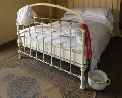 The second floor bedroom in the 1870s house in the Birmingham Back to Backs, with an iron-framed bed
