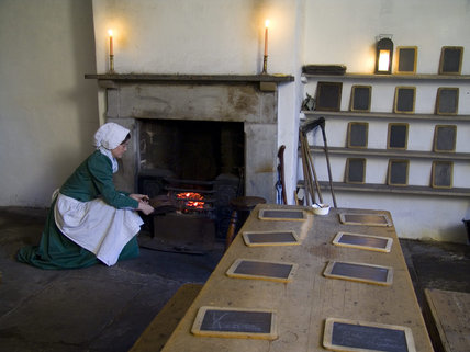 Costumed interpretors in the Apprentice House School Room at Quarry Bank Mill, Styal