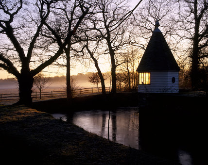 Sun glowing through the summerhouse windows at Sissinghurst Castle Garden, with silhouetted trees, frozen water and  morning mist