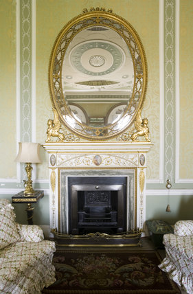 The chimney-piece with inset copper plaques in the manner of Angelica Kauffmann is probably by William Tyler in The Boudoir at Belton House, Lincolnshire, UK with the overmantel mirror reflecting the pasterwork ceiling
