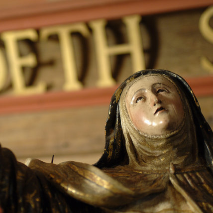 A carved wooden sculpture c. 1700  of St Therese de Avila with robes painted in gold, black and brown. St Therese founded the Order of Barefooted Carmelites. The sculpture is in Nadir at Snowshill Manor.