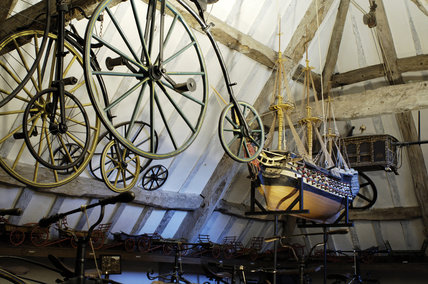 Penny-farthing bicycles and a model of HM Britannia, part of the collection of Charles Wade in Hundred Wheels at Snowshill Manor