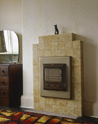 1930's electric fire fitted into a tiled fireplace in a ...