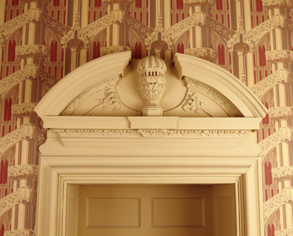 Detail of the enriched doorcase in the Gothick Corridor at Hanbury Hall, Worcestershire, with pierced urns set in broken segmental pediments