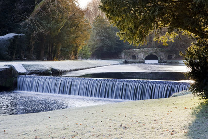 The Drum Fall and Rustic Bridge in winter at Studley Royal Water Garden, adjoining the estate at Fountains Abbey, North Yorkshire