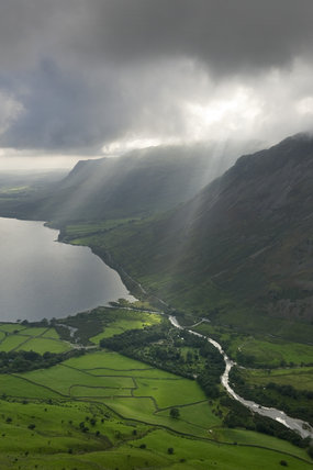 Striking and dramatic lighting over Wastwater with the National Trust camspite at Wasdale Head visible on the valley floor beside the river, Cumbria