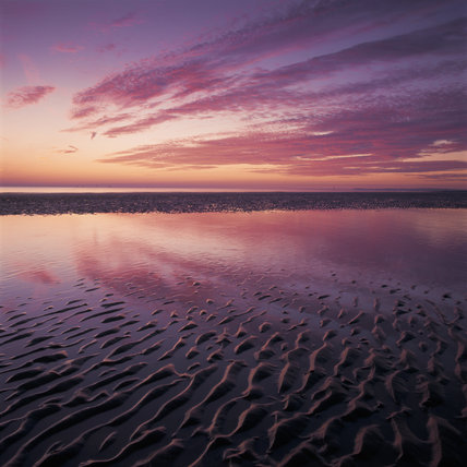 Sunset afterglow on the clouds & textured sand of Crosby beach
