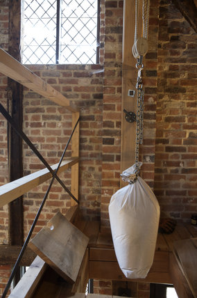 Flour sacks being hoisted and lowered in the C18th working Winchester City Mill, Hampshire where corn is ground into flour