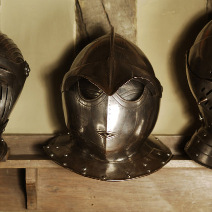 Row of helmets from C16th and C17th suits of armour, in the room known as Dragon at Snowshill Manor
